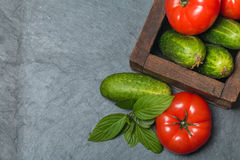 Cucumbers and Tomatoes in wooden box. Arrangement of Raw  Cucumbers and Tomatoes in wooden box on black stone background, top view Royalty Free Stock Images