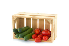 Cucumbers and tomatoes in a wooden crate Stock Photos