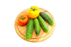 Cucumbers and tomatoes on wooden cutting board Stock Images