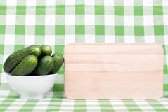 Cucumbers in a white bowl on a checkered napkin beside cutting b Royalty Free Stock Photo