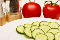 Cucumbers on White Plate with Tomatoes Royalty Free Stock Images