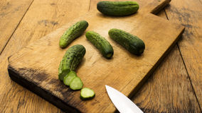Cucumbers on wooden chopping board and table. Several cucumbers on wooden chopping board and table. High resolution image Royalty Free Stock Photo