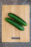 Cucumbers on wooden cutting board Royalty Free Stock Photography
