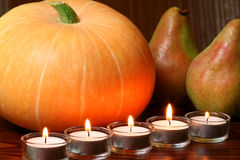 Cucurbit and pears in fire light. Pumpkin, pears and candles. Autumn atmosphere Stock Photography