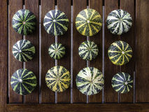 Cucurbita pepo still life green pumkins organized. Still life with variety of green and yellow pumpkins cucurbita pepo organized on wooden table, useable as Stock Photos