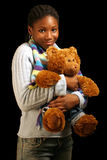 Cuddle. A teenage girl hugging a teddy bear. Isolated on a black background Royalty Free Stock Photos