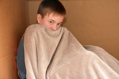 Cuddle in a box. Boy  with his woolly  cuddly blanket in a paper box Royalty Free Stock Photo