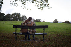 Cuddle in the Park. Young couple cuddling on a  bench in a park Royalty Free Stock Photos