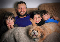 Cuddle Time. A happy daddy cuddles three smiling dark haired daughters and the family dog on the couch under a blanket Stock Images