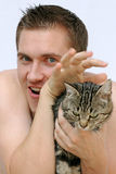 Cuddle. A young man exaggerates it with the dear to the cat Stock Photos