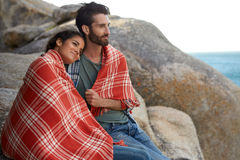 Cuddled couple sitting on the rocks, overlooking the ocean Royalty Free Stock Image