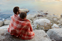 Cuddled couple sitting on the rocks, overlooking the ocean Stock Photos