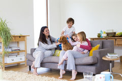 Cuddles at Home with the Dog. Same sex family together on the sofa in the living room of their home. The mothers and their two children are petting the dog who Stock Photography
