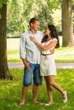 Cuddling boyfriend and girlfriend in park. Cuddling boyfriend and girlfriend standing in park royalty free stock photos