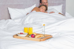 Cuddling couple asleep with breakfast tray on bed Royalty Free Stock Photography