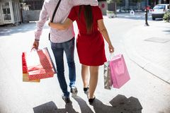 Cuddling Couple In Love going for shopping. Beautiful young couple in love going on a shopping spree in the city on a sunny day Stock Photo