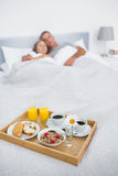 Cuddling couple sleeping with breakfast tray on bed royalty free stock photos