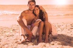 Cuddling couple smiling at camera Royalty Free Stock Photo