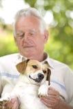 Cuddly dog. Cute dog enjoying cuddling of his elder owner Stock Image