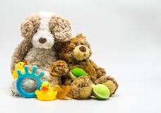 2 cuddly stuffed teddy bears leaning on each other surrounded by baby toys. 2 plush brown teddy bears leaning on each other, with a baby rattle, teething ring Stock Image