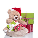 Cuddly teddy bear wearing Christmas hat and gift boxes on white Stock Photography