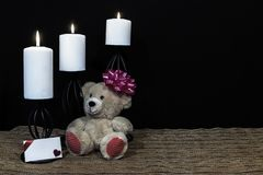 Cudlely teddy bear with pink bow on head, white candles perched on black candle holders on mesh place mat and wooden table with ca stock photos