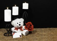 Cudlely teddy bear with red bow tie, red rose, white candles perched on black candle holders on mesh place mat and wooden table wi. Th card and dark background royalty free stock photos
