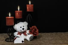 Cudlely teddy bear with red bow tie, red rose, red candles perched on black candle holders on mesh place mat and wooden table with. Card and dark background royalty free stock image