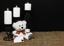 Cudlely teddy bear with red bow tie, white candles perched on black candle holders on mesh place mat and wooden table with card an. D dark background. Valentines royalty free stock photography