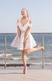 Cudowna dama pozuje na tarasie Uśmiechnięta kobieta na jaskrawym nieba tle Elegancka dziewczyna w krótkiej biel sukni obraz royalty free
