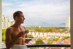 cudowny dzie? Przystojna rozochocona facet pozycja na balkonie pod pięknym niebem i cieszyć się pogodnego ranek zdjęcie stock
