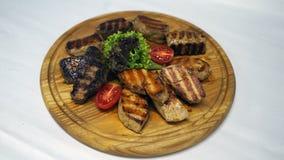 Cudowny mięsny naczynie gotujący na grillu z i rozkładający na drewnie ziobro soczystymi i liśćmi sałata fotografia stock