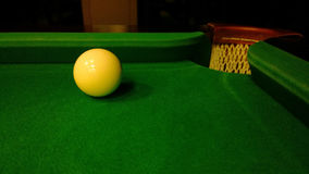 The cue ball left on the Board next to the billiard pocket Royalty Free Stock Images