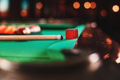 Cue and chalk on a pool table. Stock Photos