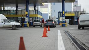 Cue at Petrol Station. Cars and people at the filling station wait in line to pump to refuel with combustible. Suitable video for a wide range of subjects like stock footage