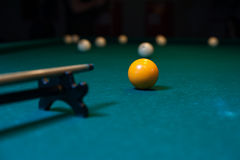 Cue and snooker balls, billiard game background. Billiard cue is aiming to take the snooker shot. Green table with balls on background Stock Photo