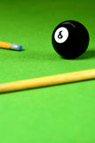 Cue stick and snooker ball. S over green surface, shallow depth of field Stock Photos