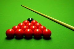 Cue stick and snooker balls. Over green surface, shallow depth of field stock image
