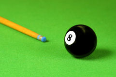 Cue stick and snooker balls. Over green surface, shallow depth of field Royalty Free Stock Photography