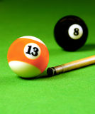 Cue stick and snooker balls. Over green surface, shallow depth of field Royalty Free Stock Photo