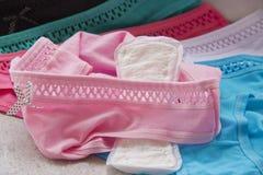 A cuecas e as almofadas sanit?rias das mulheres coloridas fotografia de stock