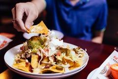 Cueillez à la main la salade de Nacho avec le chou coupé en tranches, le piment mariné, le scoop de l'avocat et le fromage s'habi photos libres de droits