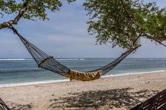 Cuelgue svinging de una hamaca entre dos árboles en la playa tropical Foto de archivo libre de regalías