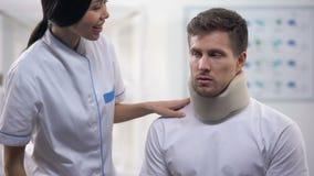 Cuello cervical de fijación de la espuma paciente masculina del cirujano atento después del trauma, rehabilitación almacen de metraje de vídeo