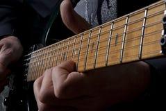 Cuello de la guitarra con los fingeres que lo juegan Imagen de archivo