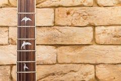 Cuello de la guitarra y fondo del ladrillo fotografía de archivo