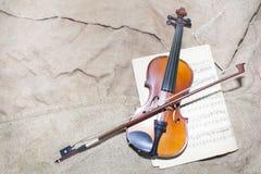 Cuello del violín en fondo de los papeles de música Fotos de archivo