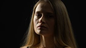 Cuello femenino joven de la cara que frota ligeramente y mirada abajo, luchando con inseguridades almacen de video