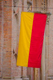 Cuenca, Ecuador - April 22, 2015: Closeup yellow and red Cuenca flag hanging down from pole attached to brick building Stock Images