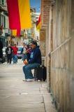 Cuenca, Ecuador - 22. April 2015: Straßenausführender, der zurück gegen Wand auf den Verstärker singt in den Stadtstraßen sitzt Lizenzfreies Stockfoto
